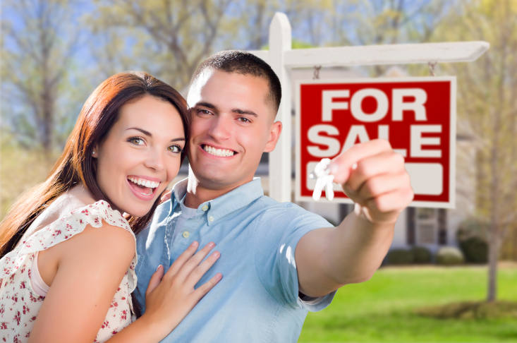 Couple In Front of New Home with New House Keys and For Sale Real Estate Sign Outside.